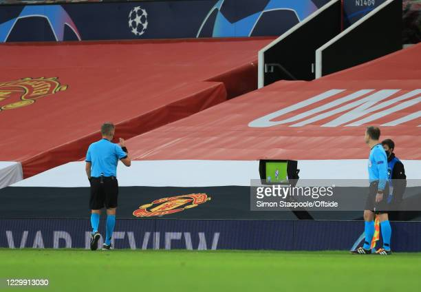 Referee Daniele Orsato checks the VAR replay of the incident between Fred of Manchester United and Leandro Paredes of PSG during the UEFA Champions...