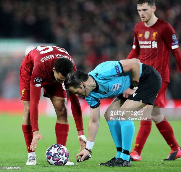 Referee Danny Makkelie applies vanishing spray ahead of a freekick to be taken by Liverpool's Trent AlexanderArnold during the UEFA Champions League...