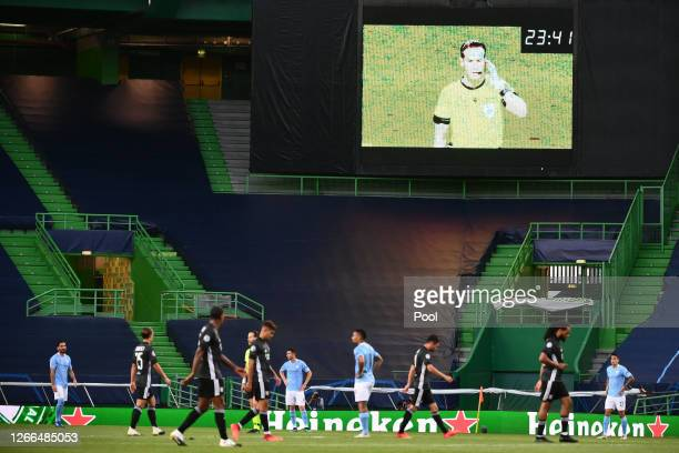 Referee Danny Makkelie is seen on the big screen using his earpiece during the UEFA Champions League Quarter Final match between Manchester City and...