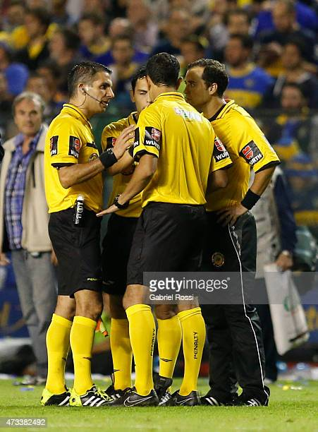 Referee Dario Herrera talks to his assitants after a tear gas bomb was thrown by fans of Boca Juniors during a second leg match between Boca Juniors...