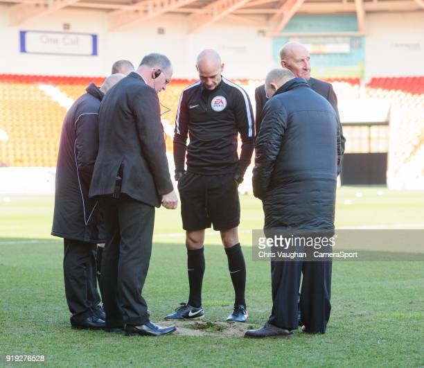 Referee Darren Drysdale centre inspects a hole which appeared in Doncaster Rovers Keepmoat Stadium pitch after the water sprinklers were switched on...