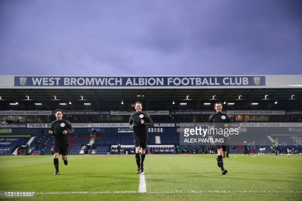 Referee Darren England and his assistants warm up for the English Premier League football match between West Bromwich Albion and Everton at The...