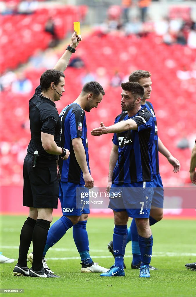 Referee Darren England shows a yellow card to Liam Davis of Cleethorpes Town during The Buildbase FA Vase Final between South Shields and Cleethorpes Town at Wembley Stadium on May 21, 2017 in London, England.