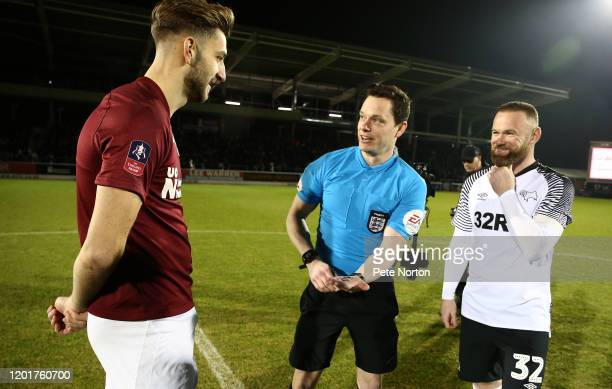 Referee Darren England shows Northampton Town captain Charlie Goode the coin at the coin toss as Derby County captain Wayne Rooney looks on smiling...