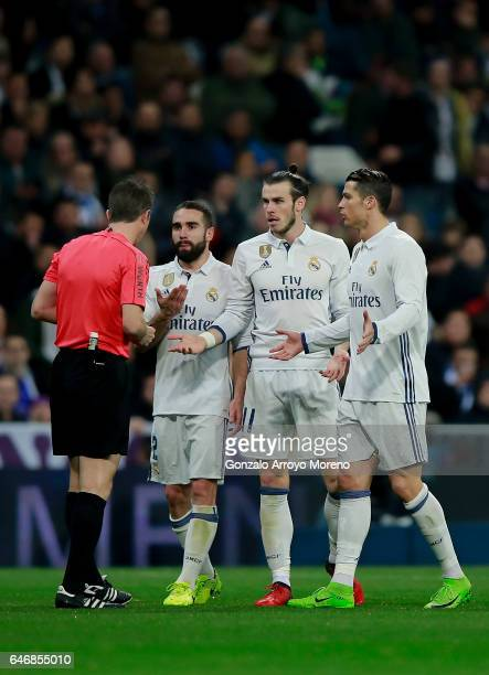 Referee David Fernandez Borbalan argues with Real Madrid players Cristiano Ronaldo Gareth Bale and Daniel Carvajal after having shown the red card to...