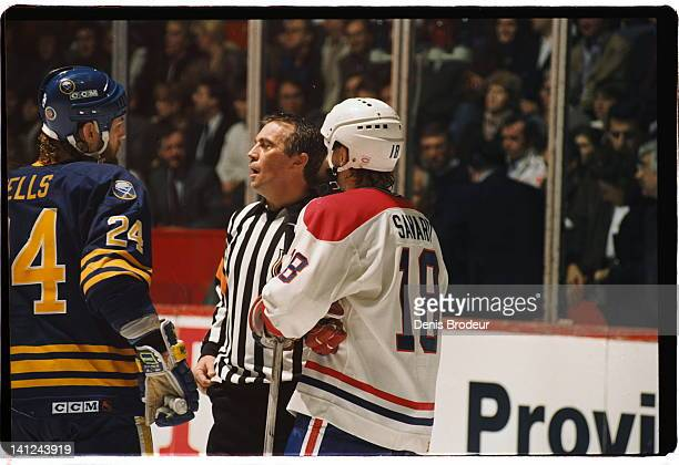 Referee Denis Morel talks to Denis Savard of the Montreal Canadiens and Jay Wells of the Buffalo Sabres Circa 1990 Montreal Quebec Canada