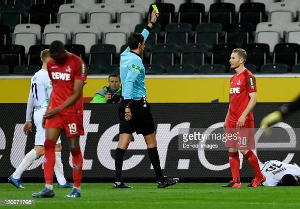 Referee Deniz Aytekin and Florian Kainz of 1. FC Koeln shows the yellow card during the Bundesliga match between Borussia Moenchengladbach and 1. FC...