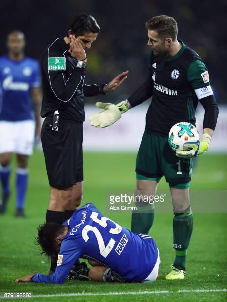 Referee Deniz Aytekin and goalkeeper Ralf Faehrmann of Schalke look after Amine Harit during the Bundesliga match between Borussia Dortmund and FC...