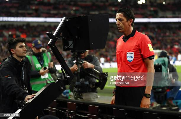 Referee Deniz Aytekin checks the VAR during the International Friendly match between England and Italy at Wembley Stadium on March 27 2018 in London...