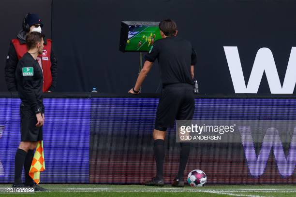 Referee Deniz Aytekin checks the VAR monitor during the German first division Bundesliga football match between 1. FC Union Berlin vs FC Cologne in...