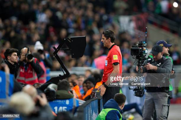 Referee Deniz Aytekin consults the VAR system during the International Friendly match between England and Italy at Wembley Stadium on March 27 2018...