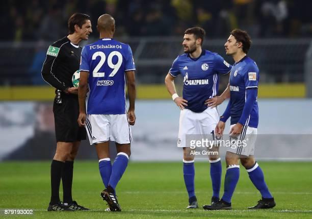 Referee Deniz Aytekin discusses with Naldo Daniel Caligiuri and Benjamin Stambouli of Schalke during the Bundesliga match between Borussia Dortmund...