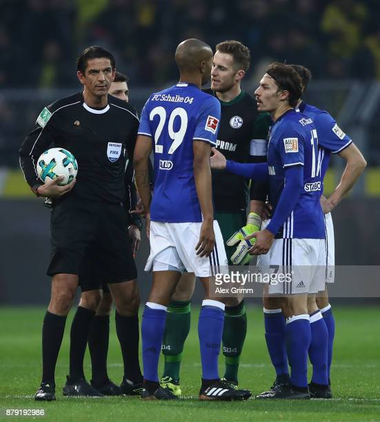 Referee Deniz Aytekin discusses with Ralf Faehrmann Naldo Daniel Caligiuri and Benjamin Stambouli of Schalke during the Bundesliga match between...