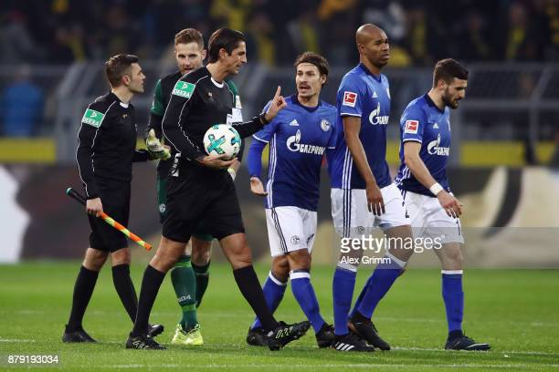 Referee Deniz Aytekin discusses with Ralf Faehrmann Naldo Daniel Caligiuri and Benjamin Stambouli of Schalke during the Bundesliga match between...