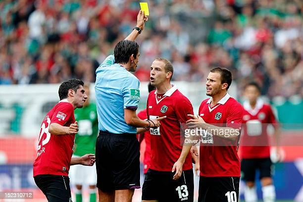 Referee Deniz Aytekin show yellow card Jan Schlaudraff of Hannover during the 1 Bundesliga match between Hannover 96 and Werder Bremen at AWD Arena...