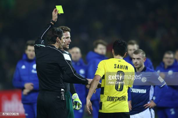 Referee Deniz Aytekin shows a yellow card to both Nuri Sahin of Dortmund and Ralf Faehrmann of Schalke after the Bundesliga match between Borussia...