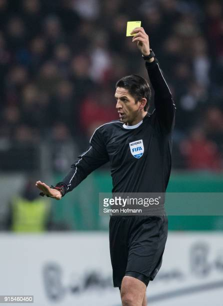Referee Deniz Aytekin shows the yellow card during the DFB Cup quarter final match between Eintracht Frankfurt and 1 FSV Mainz 05 at CommerzbankArena...