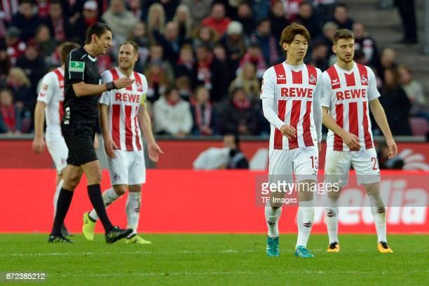 Referee Deniz Aytekin speaks with Matthias Lehmann of FC Koeln and Yuya Osako of FC Koeln and Salih Oezcan of FC Koeln look on during the Bundesliga...
