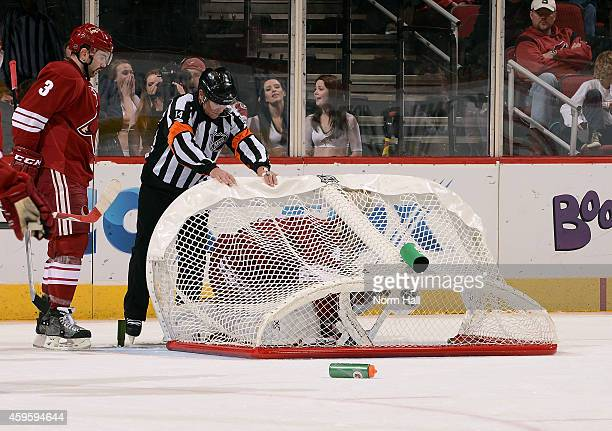 Referee Dennis LaRue tries to assist goaltender Mike Smith of the Arizona Coyotes after teammate Keith Yandle knocked over the net during overtime...