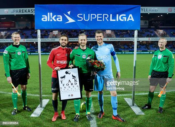 Referee Dennis Mogensen receiving gifts from captain Jakob Poulsen of FC Midtjylland and Mads Agesen of Randers FC prior to his last match which was...
