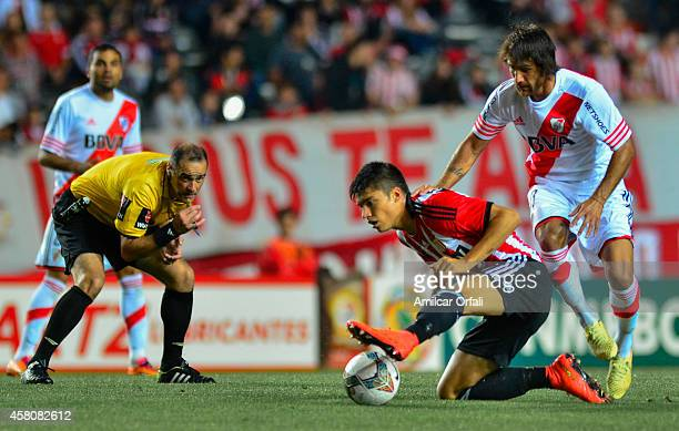 Referee Diego Abal looks a play between and Joaquin Correa of Estudiantes and Leonardo Ponzio of River Plate during a first leg match between...