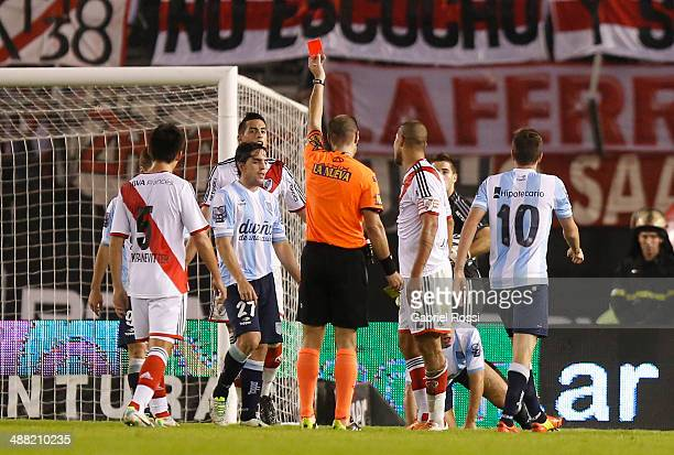 Referee Diego Abal shows the red card to Jonathan Maidana of River Plate during a match between River Plate and Racing Club as part of 17th round of...