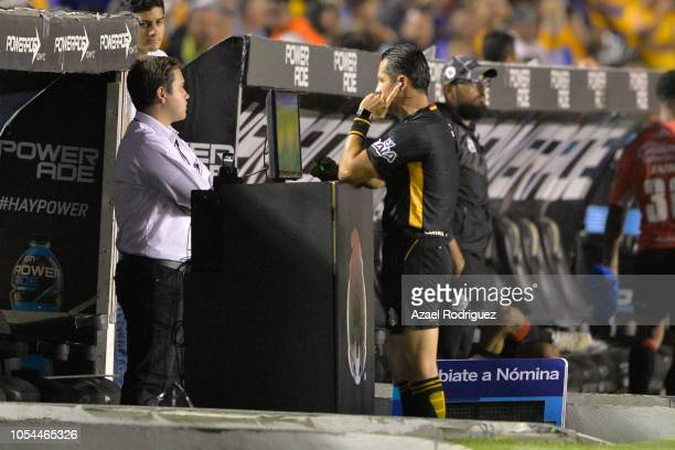 Referee Diego Montano verifies the validity of Francisco 'Maza' Rodriguez's goal through the VAR during the 14th round match between Tigres UANL and...