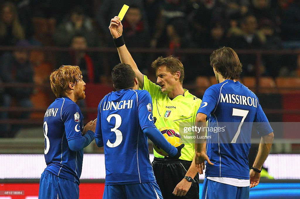 Referee Dino Tommasi (C) shows the yellow card to Davide Biondini (L) of US Sassuolo Calcio during the TIM Cup match between AC Milan and US Sassuolo Calcio at Stadio Giuseppe Meazza on January 13, 2015 in Milan, Italy.