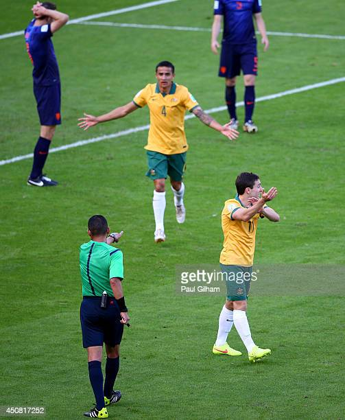 Referee Djamel Haimoudi signals for a penalty kick as Tim Cahill and Tommy Oar of Australia react during the 2014 FIFA World Cup Brazil Group B match...