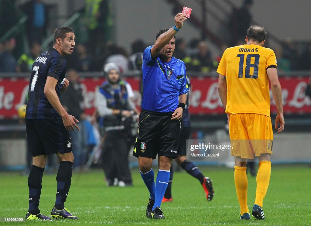 Referee Domenico Celi (C) shows the red card to Vangelis Moras (R) of Hellas Verona FC at the end of the Serie A match between FC Internazionale Milano and Hellas Verona at Stadio Giuseppe Meazza on October 26, 2013 in Milan, Italy.