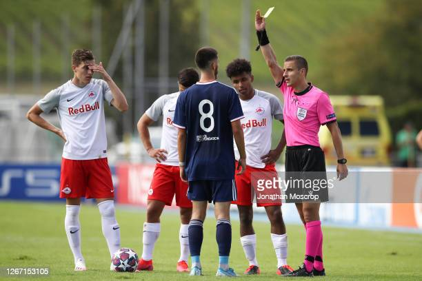 Referee Donatas Rumsas shows a yellow card to both Noam Bonnet of Lyon and Karim Adeyemi of Salzburg following an altercation between the two during...