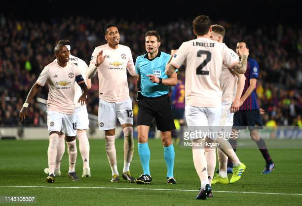 Referee Dr Felix Brych is surrounded by Manchester United players as they appeal to the referee during the UEFA Champions League Quarter Final second...