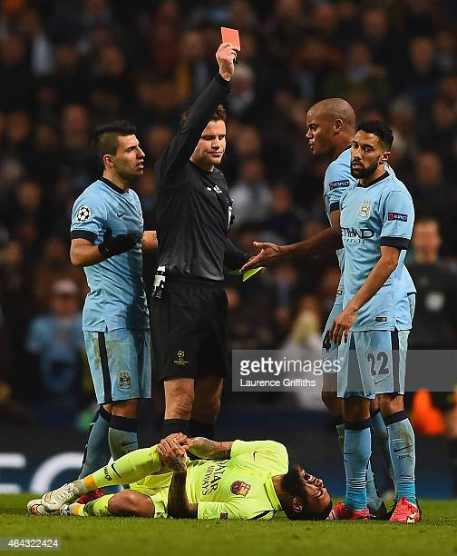 Referee Dr Felix Brych shows Gael Clichy of Manchester City a red card during the UEFA Champions League Round of 16 match between Manchester City and...
