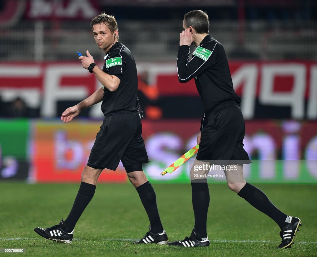 Referee Dr. Jochen Drees returns the pitch after a break in the match during the Second Bundesliga match between 1. FC Union Berlin and 1. FC Nuernberg at Stadion An der Alten Foersterei on March 20, 2017 in Berlin, Germany.