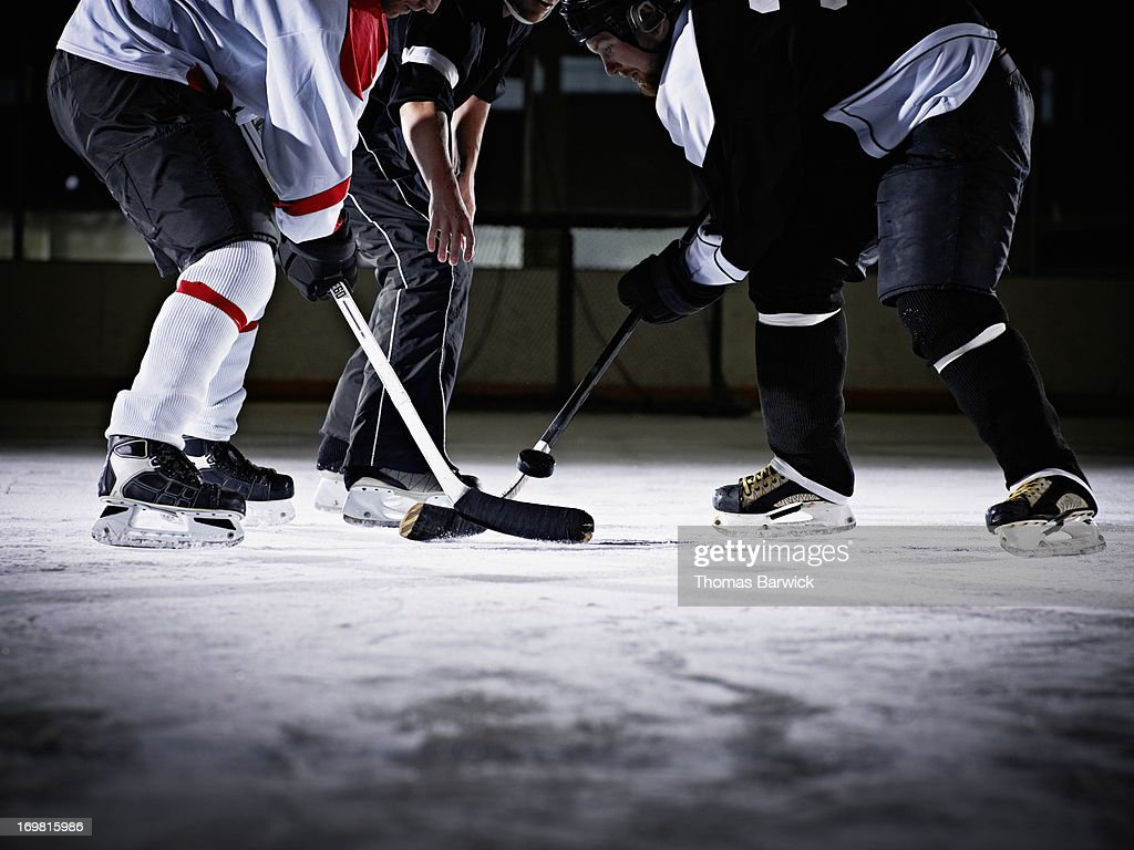 Referee dropping hockey puck for faceoff : Stock Photo