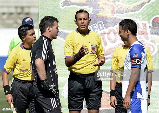 Referee Eder Vergara speaks with the captains of both teams Alexis Viera of America de Cali and Daniel Cataño of Rionegro during the formal events...
