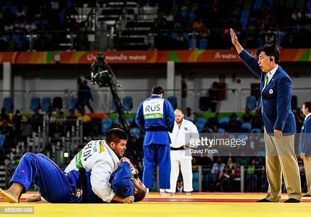 Referee Edison Minakowa of Brazil raises his arm to signal ippon after Barna Bor of Hungary held Faicel Jaballah of Tunisia for 20 seconds to win...