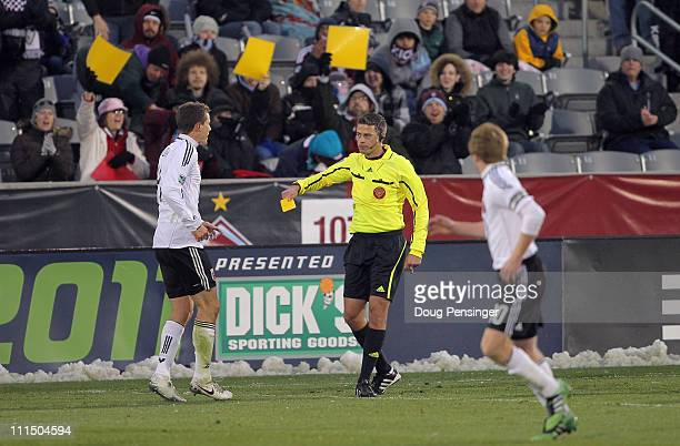 Referee Elias Bazakos gives a yellow card to Marc Burch of D.C. United for a foul against the Colorado Rapids as the fans present yellow cards of...