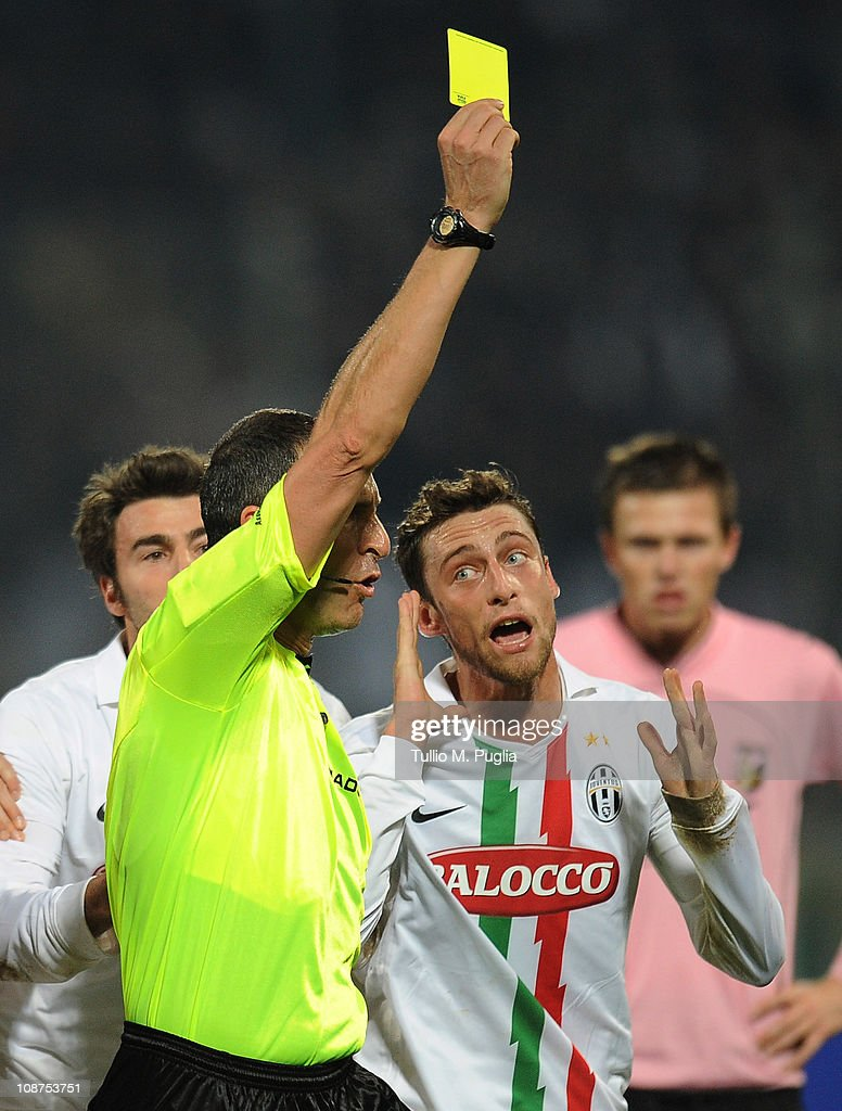 Referee Emidio Morganti issues a yellow card to Claudio Marchisio of Juventus during the Serie A match between US Citta di Palermo and Juventus FC at Stadio Renzo Barbera on February 2, 2011 in Palermo, Italy.