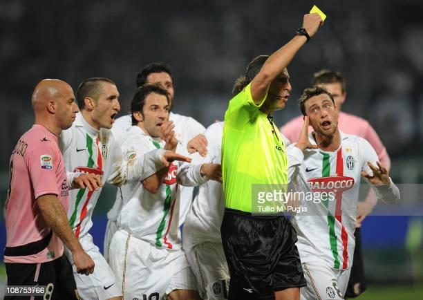 Referee Emidio Morganti issues a yellow card to Claudio Marchisio of Juventus during the Serie A match between US Citta di Palermo and Juventus FC at...