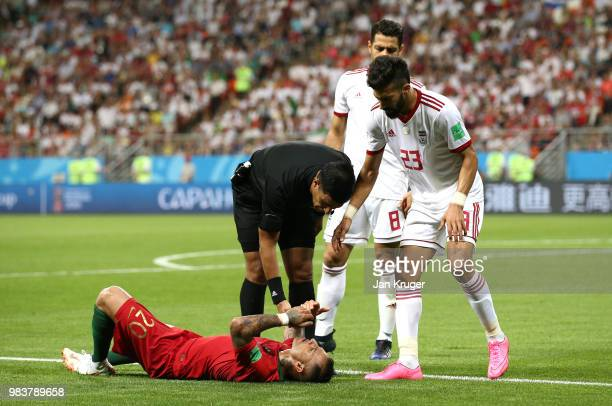 Referee Enrique Caceres anf Ramin Rezaeian of Iran check conditions of Ricardo Quaresma of Portugal during the 2018 FIFA World Cup Russia group B...