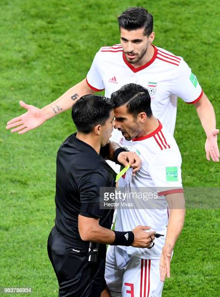 Referee Enrique Caceres books Ehsan Haji Safi of Iran as Iran players complain about his decision to award Portugal a penalty during the 2018 FIFA...