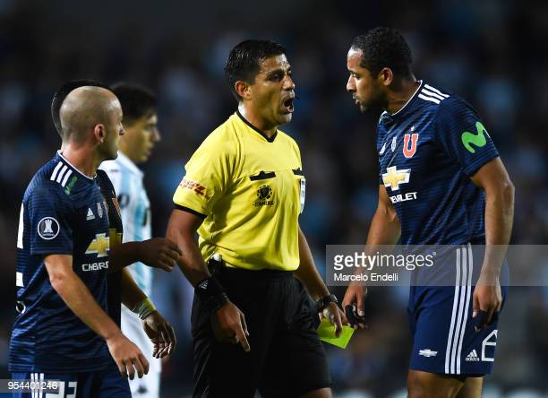 Referee Enrique Caceres of Paraguay argues with Jean Beausejour of Universidad de Chile during a group stage match between Racing Club and...