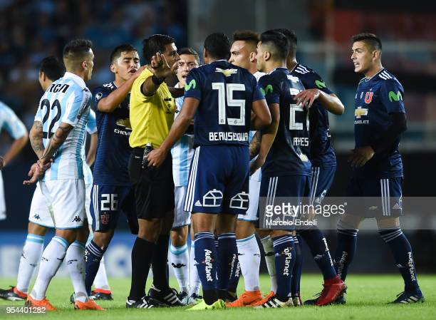 Referee Enrique Caceres of Paraguay argues with players of Racing Club and Universidad de Chile during a group stage match between Racing Club and...