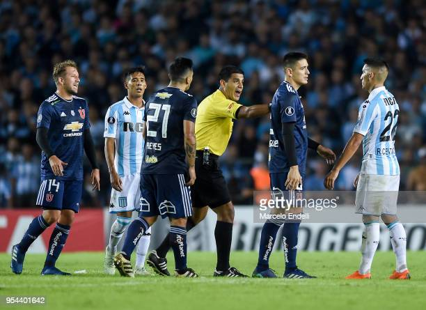 Referee Enrique Caceres of Paraguay argues with Ricardo Centurion of Racing Club during a group stage match between Racing Club and Universidad de...