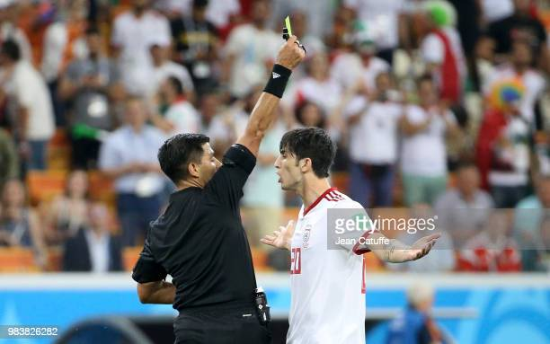 Referee Enrique Caceres of Paraguay gives a yellow card to Sardar Azmoun of Iran during the 2018 FIFA World Cup Russia group B match between Iran and...