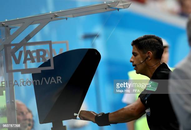 Referee Enrique Caceres reviews the VAR footage before awarding Portugal a penalty during the 2018 FIFA World Cup Russia group B match between Iran...