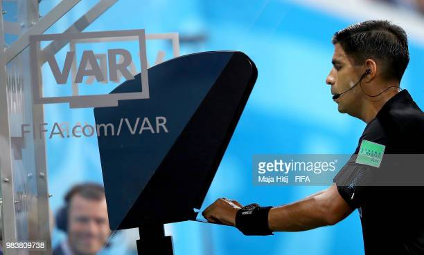 Referee Enrique Caceres reviews the VAR footage before giving a yellow card to Cristiano Ronaldo of Portugal during the 2018 FIFA World Cup Russia...