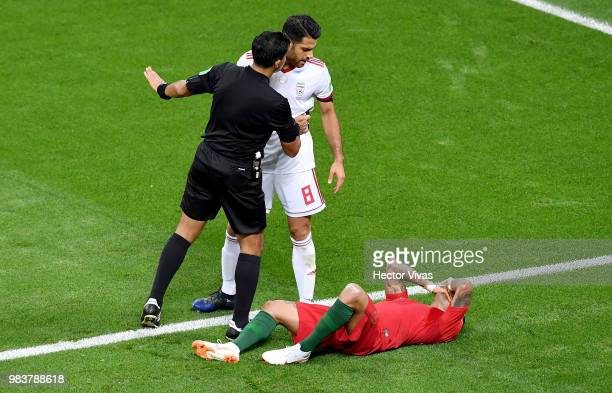 Referee Enrique Caceres talks to Morteza Pouraliganji of Iran while Ricardo Quaresma of Portugal lies on the pitch injured during the 2018 FIFA World...