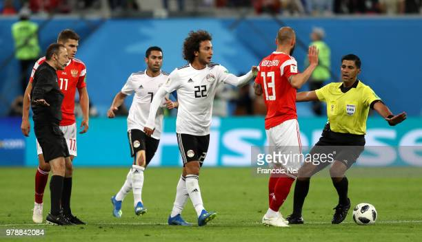 Referee Enrique Caceres tries to calm Fedor Kudriashov of Russia and Amr Warda of Egypt during the 2018 FIFA World Cup Russia group A match between...